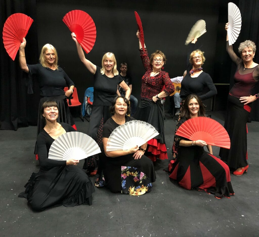 Ladies in Flamenco costume all holding up fans and smiling