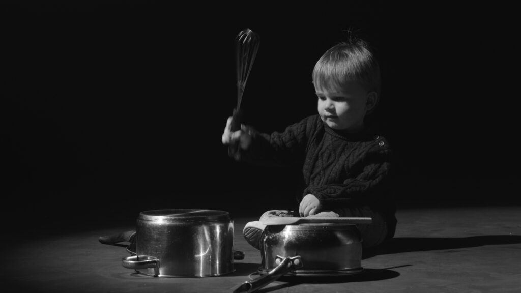 A little boy hitting pots and pans with a whisk, like drums