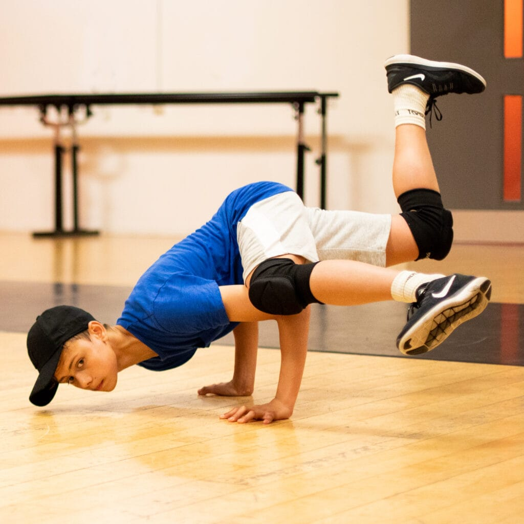 Boy in black cap and blue tshirt doing a breakdance move